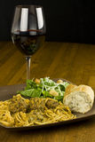 Spaghetti, Salad, and Wine. A plate of spaghetti with meatballs and a side salad with red wine Royalty Free Stock Photography