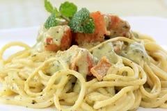 Spaghetti and salmon in pesto sauce Stock Images