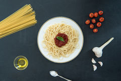 Spaghetti with sauce, basil and ingredients on black Royalty Free Stock Image