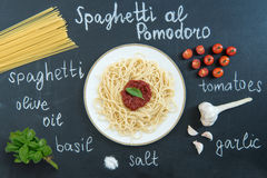 Spaghetti with sauce, basil and ingredients on black Stock Photography