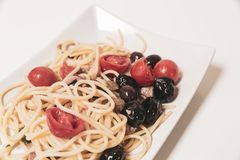 Spaghetti with sauce consisting of: cherry tomatoes, capers, oli Stock Image
