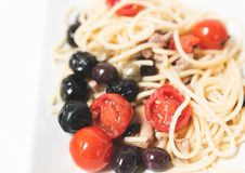 Spaghetti with cherry tomatoes, capers, olives. Royalty Free Stock Images