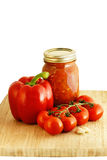 Spaghetti sauce ingredients and preserve. Yummy homemade spaghetti sauce preserve, red vine tomatoes, red pepper and garlic on bamboo cutting board Royalty Free Stock Photography