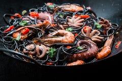 Spaghetti savoureux avec des fruits de mer faits de poulpe, crevettes roses de tigre Photo libre de droits