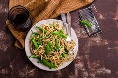 Spaghetti scuri con i piselli Immagini Stock
