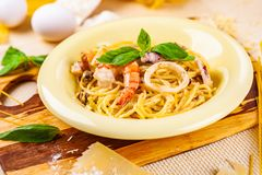 Spaghetti with seafood and parmesan cheese in beige plate stock photos