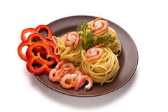 Spaghetti with shrimp and pepper. Spaghetti with shrimp and red pepper in a clay dish Stock Photos
