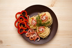 Spaghetti with shrimp. And red pepper in a dish on the table Royalty Free Stock Images