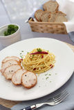 Spaghetti with slicing meat. And bread basket Royalty Free Stock Photography