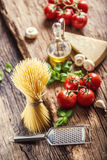 Spaghetti.Spaghetti tomatoes basil olive oil parmesan cheese and mushrooms on very old oak board. Stock Photography