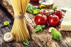 Spaghetti.Spaghetti tomatoes basil olive oil parmesan cheese and mushrooms on very old oak board. Royalty Free Stock Photo
