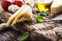 Spaghetti.Spaghetti tomatoes basil olive oil parmesan cheese and mushrooms on very old oak board. Royalty Free Stock Photography