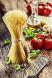 Spaghetti.Spaghetti tomatoes basil olive oil parmesan cheese and mushrooms on very old oak board. Stock Images
