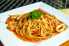 Spaghetti with squid , shrimps and Tomato Sauce Stock Photos