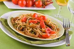 Spaghetti with squids, peas and cherry tomatoes. Royalty Free Stock Photography