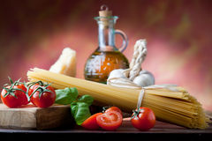 Spaghetti Still LIfe. Raw pasta with tomato, basill, garlic, Parmesan cheese and olive oil close up Stock Photos