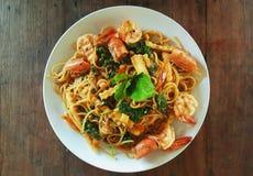 Spaghetti stir fried spicy thai pad ki mao with shrimp on wooden table stock photo