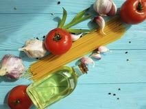 Spaghetti suszący pomidorowy czosnek, pieprz, olej na błękitnym drewnianym tle Zdjęcia Stock