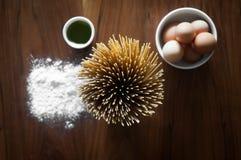 Spaghetti-Teigwaren mit Bestandteilen im Hintergrund lizenzfreie stockfotos