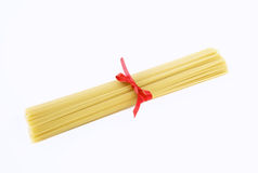Spaghetti tied with a red bow. On white stock photography
