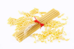 Spaghetti tied with a red bow and other pasta. On white stock photography