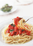 Spaghetti with tomato and basil on fork close up Royalty Free Stock Images