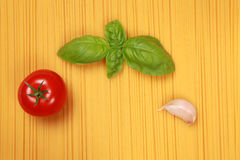 Spaghetti with tomato, garlic and basil. On a background of spaghettis there is a tomato, basil and garlic stock image