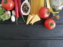Spaghetti, tomato, garlic, cheese pasta organic menu a black wooden background. Spaghetti tomato garlic cheese on a black wooden background menu organic pasta royalty free stock photography