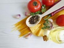 Spaghetti, tomato, garlic, cheese red pepper traditional a white wooden background. Spaghetti tomato garlic red pepper cheese on a white wooden background menu stock photos