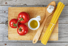 Spaghetti tomato garlic oil. Ingredients on wood background Stock Images