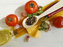 Spaghetti, tomato, garlic, cheese red pepper vegetarian a white wooden background. Spaghetti tomato garlic red pepper cheese on a white wooden background menu royalty free stock photo