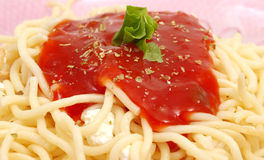 Spaghetti with tomato sauce. In a red dish Royalty Free Stock Photography
