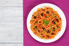 Spaghetti with tomato sauce, capers and olives. Pasta spaghetti with tomato sauce, capers and olives on plate on  wooden background, traditional Italian recipe Royalty Free Stock Image
