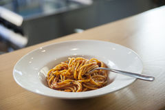 Spaghetti in tomato sauce with fork. White ceramic plate on wooden shelf Royalty Free Stock Photos