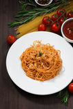 Spaghetti with tomato sauce and ingredients on a wooden table Royalty Free Stock Images