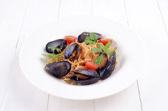 Spaghetti in tomato sauce with mussels and fresh coriander Stock Image