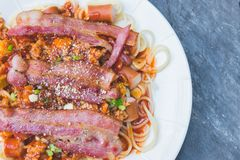Spaghetti with tomato sauce and sausage with bacon in white dish. Stock Photos