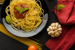 Spaghetti with tomato sauce and their ingredients around .Adjust Stock Image