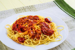 Spaghetti with tomato sauce on a white and green   tablecloth. Royalty Free Stock Images