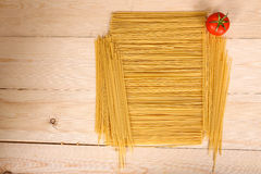 Spaghetti and tomato. On a wooden background Stock Photography