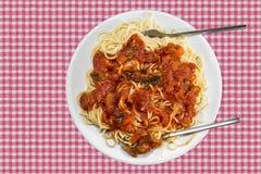 Spaghetti with tomatoe sauce. On checkered tablecloth Stock Photos