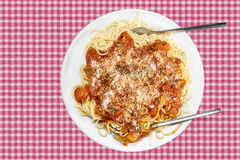 Spaghetti with tomatoe sauce and cheese. On checkered tablecloth Royalty Free Stock Images