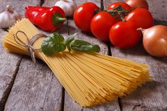 Spaghetti, tomatoes and basil on old table closeup. Ingredients for pasta Stock Photo