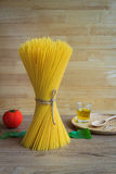 Spaghetti and tomatoes with basil and olive oil on wooden table Stock Photography