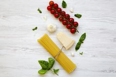 Spaghetti, tomatoes, basil, parmesan, garlic. Ingredients for cooking italian pasta on a white wooden table, flat lay. From above Royalty Free Stock Photo