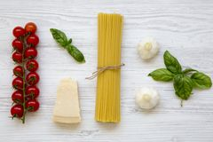 Spaghetti, tomatoes with basil, parmesan, garlic. Ingredients for cooking pasta on a white wooden background, flat lay. From above royalty free stock photo