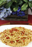 Spaghetti with Tomatoes and Flowers. White plate full of delicious durum wheat spaghetti with diced, organic tomatoes and herbs set on a wood tray with blue stock image