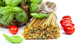 Spaghetti with  tomatoes, and fresh basil leaves. Royalty Free Stock Image