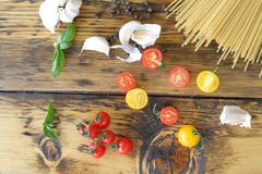 Spaghetti, tomatoes and garlic on a wooden table Royalty Free Stock Photos
