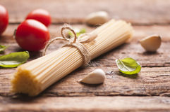 Spaghetti. And tomatoes with herbs on an old and vintage wooden table Stock Images